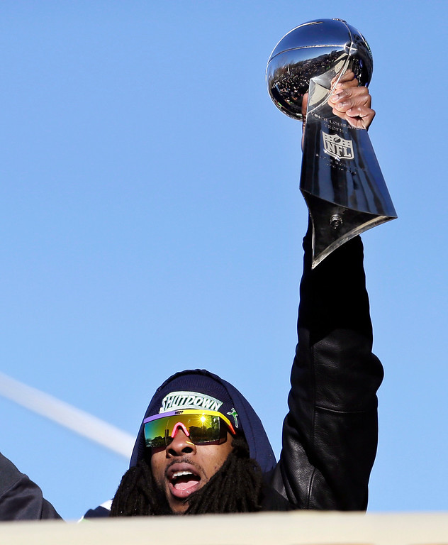 . Seattle Seahawks\' Richard Sherman holds up the Vince Lombardi Trophy during a parade for the NFL football Super Bowl champions Wednesday, Feb. 5, 2014, in Seattle. (AP Photo/Elaine Thompson)