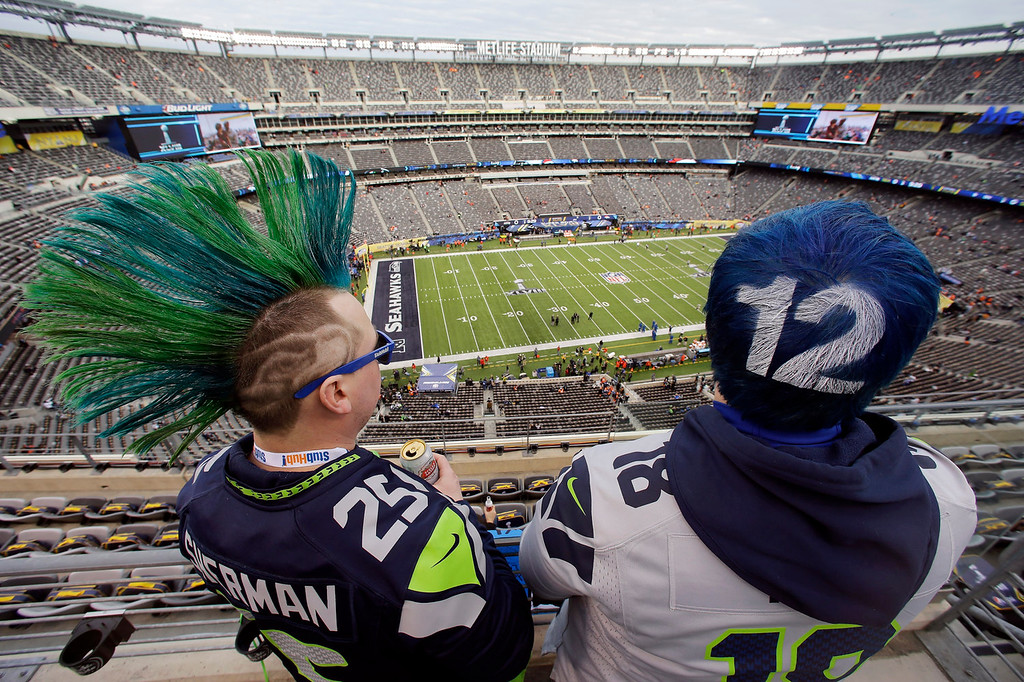 . Seattle Seahawks fans John Hanshaw, left, and Pete Ford, both of Tacoma, Wash., watch the field before the NFL Super Bowl XLVIII football game between the Seattle Seahawks and the Denver Broncos, Sunday, Feb. 2, 2014, in East Rutherford, N.J. (AP Photo/Mel Evans)