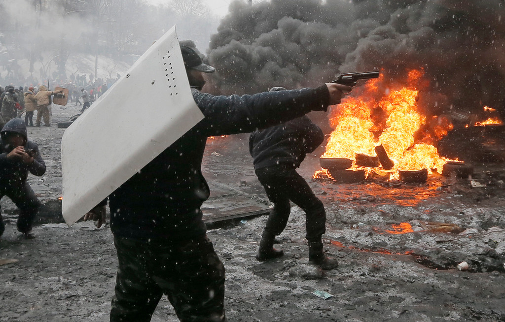 . A protester points a handgun during a clash with police in central Kiev, Ukraine, Wednesday, Jan. 22, 2014.  (AP Photo/Efrem Lukatsky)