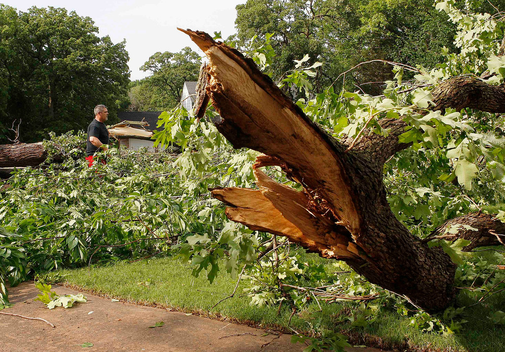 . Bob Cameron of Edmond, Oklahoma, helps a neighbor move downed trees after a tornado swept through the eastern part of Edmond, Oklahoma May 19, 2013. A tornado half a mile wide struck near Oklahoma City on Sunday, part of a massive storm front that hammered the central United States. News reports said at least one person had died. REUTERS/Bill Waugh