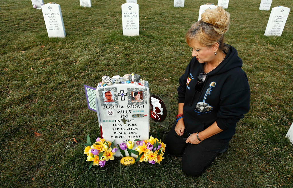 . Celeste Mills of El Paso, Texas, kneels beside the grave of her youngest son, Joshua Mills, who was killed in Afghanistan, at Arlington National Cemetery in Virginia, March 13, 2013. Picture taken March 13, 2013. REUTERS/Kevin Lamarque