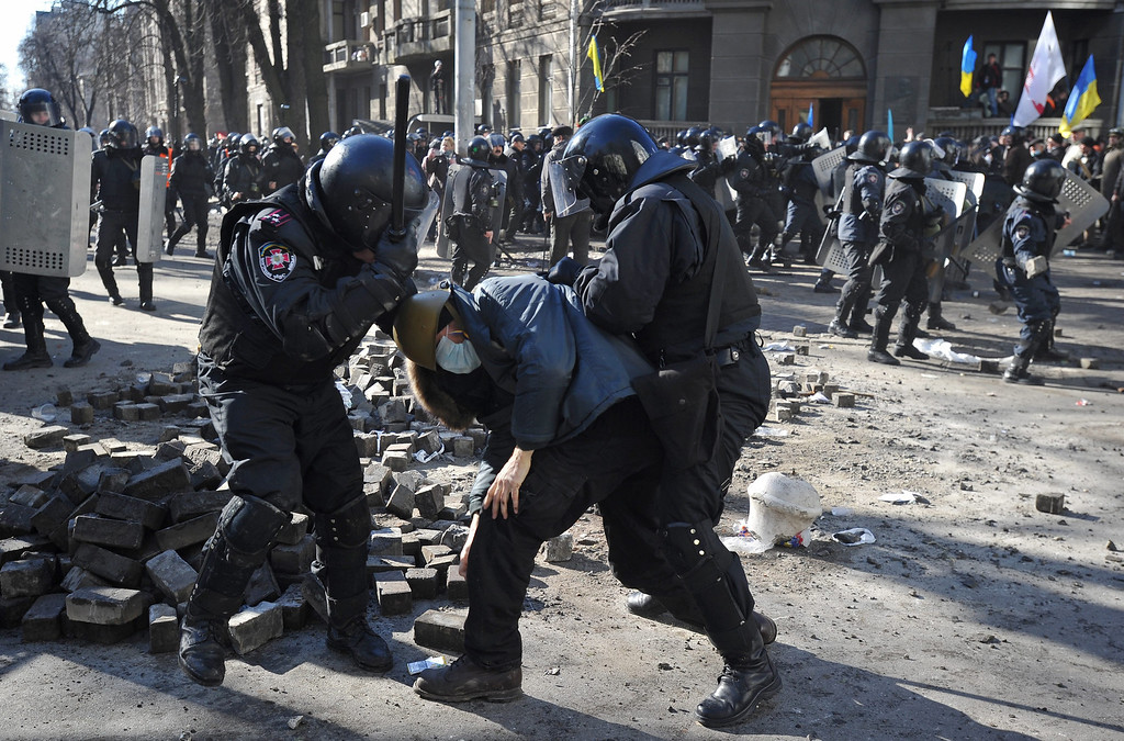. Riot police detain a protester during an anti-government protest in downtown Kiev, Ukraine, 18 February 2014. A least three protesters were killed in clashes with police on 18 February, Ukrainian opposition activists say. Violence erupted in the Ukrainian capital after anti-government protesters broke through a police cordon in front of parliament.   EPA/ALEXEY FURMAN