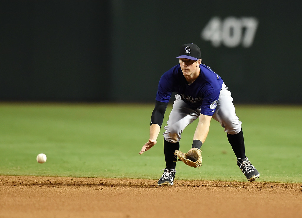. DJ LeMahieu #9 of the Colorado Rockies makes a play on a ground ball during the seventh inning against the Arizona Diamondbacks at Chase Field on August 8, 2014 in Phoenix, Arizona.  (Photo by Norm Hall/Getty Images)