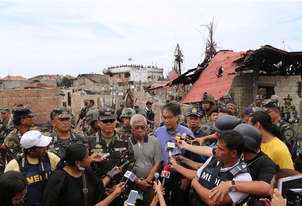 . Philippine Armed Forces Chief Gen. Emmanuel Bautista, center left, Secretary of National Defense Voltaire Gazmin, center in striped shirt, and Interior and Local Government Secretary Mar Roxas, in blue shirt, attend a press conference as they tour the site of a three-week intense fighting between Government forces and Muslim rebels who have taken nearly 200 people hostages in Zamboanga city, southern Philippines, Saturday Sept. 28, 2013. The deadly standoff between government troops and Muslim rebels has ended with all of the captives safe, officials said Saturday. Defense Secretary Voltaire Gazmin said only a handful of Moro National Liberation Front rebels remained in hiding and were being hunted by troops in the coastal outskirts of Zamboanga city, adding authorities were trying to determine if rebel commander Habier Malik, who led the Sept. 9 siege, was dead. More than 200 people were killed in the clashes, including 183 rebels and 23 soldiers and police, in one of the bloodiest and longest-running attacks by a Muslim group in the south, scene of decades-long Muslim rebellion for self-rule in the largely Roman Catholic country. (AP Photo)