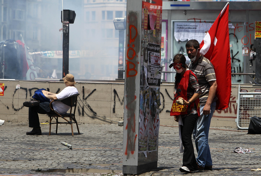. A protester sits on a chair as others take cover behind an advertising banner during clashes at the Taksim Square in Istanbul Tuesday, June 11, 2013.  (AP Photo/Thanassis Stavrakis)