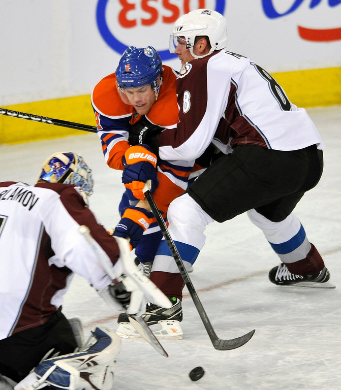 . Edmonton Oilers\' Taylor Hall (4) is checked by Colorado Avalanche\'s Jan Hejda (R) and goalie Semyon Varlamov during the first period of their NHL hockey game in Edmonton February 16, 2013. REUTERS/Dan Riedlhuber