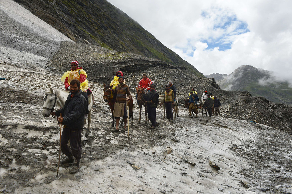 . Hindu devotees ride horses on a glacier  near Amarnath Cave on August 18, 2013. Every year, hundreds of thousands of pilgrims trek through treacherous mountains in revolt-torn Kashmir, along icy streams, glacier-fed lakes and frozen passes, to reach the Amarnath cave, located at an altitude of 3,857 meters (12,729 feet), where a Shiva Lingam, an ice stalagmite shaped as a phallus and symbolizing the Hindu God Shiva, stands for worship.   TAFATAUSEEF MUSTAFA/AFP/Getty Images