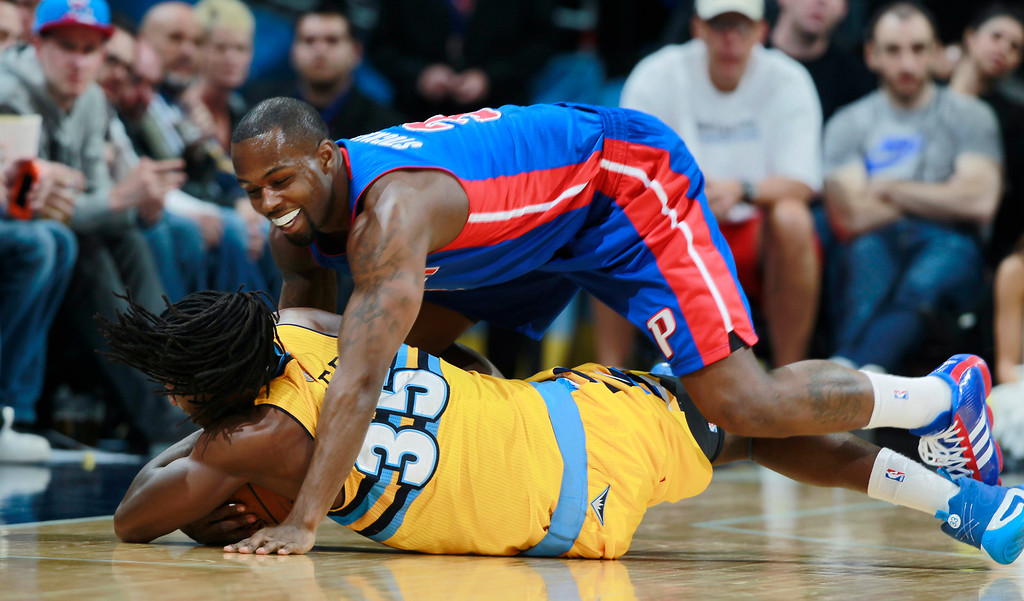 . Detroit Pistons guard Rodney Stuckey, top, falls on Denver Nuggets forward Kenneth Faried as he recovers a loose ball in the third quarter of the Nuggets\' 118-109 victory in an NBA basketball game in Denver on Wednesday, March 19, 2014. (AP Photo/David Zalubowski)