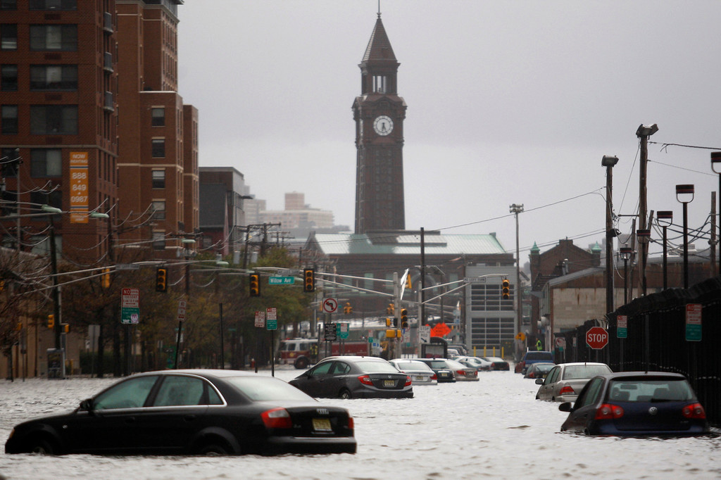 . Cars are seen on a street flooded at Hoboken in New Jersey, October 30, 2012. Millions of people across the eastern United States awoke on Tuesday to scenes of destruction wrought by monster storm Sandy, which knocked out power to huge swathes of the nation\'s most densely populated region, swamped New York\'s subway system and submerged streets in Manhattan\'s financial district.  REUTERS/Eduardo Munoz