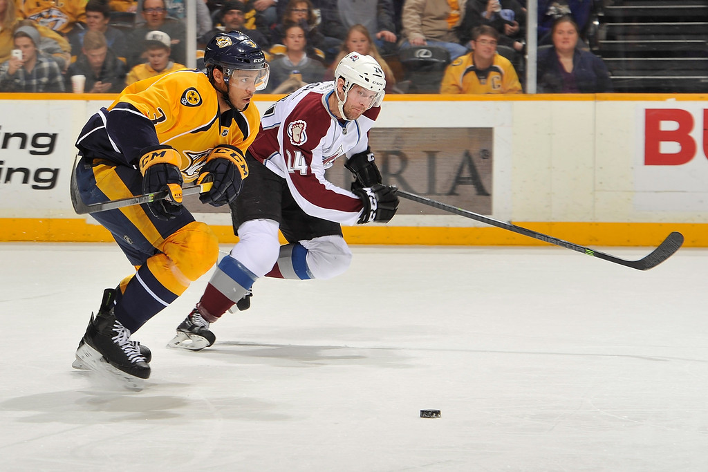. NASHVILLE, TN - JANUARY 18:  Marc-Andre Cliche #24 of the Colorado Avalanche and Seth Jones #3 of the Nashville Predators chase a loose puck at Bridgestone Arena on January 18, 2014 in Nashville, Tennessee.  (Photo by Frederick Breedon/Getty Images)