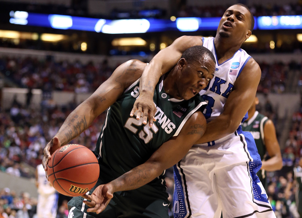. Derrick Nix #25 of the Michigan State Spartans draws contact on offense in the first half against Tyler Thornton #3 of the Duke Blue Devils during the Midwest Region Semifinal round of the 2013 NCAA Men\'s Basketball Tournament at Lucas Oil Stadium on March 29, 2013 in Indianapolis, Indiana.  (Photo by Andy Lyons/Getty Images)