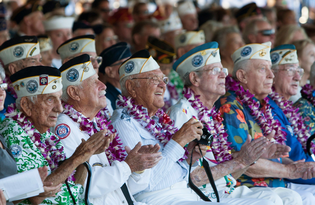 . Pearl Harbor survivors watch a vintage WWII airplane fly over Pearl Harbor at the ceremony commemorating the 72nd anniversary of the attack on Pearl Harbor, Saturday, Dec. 7, 2013, in Honolulu.  (AP Photo/Marco Garcia)