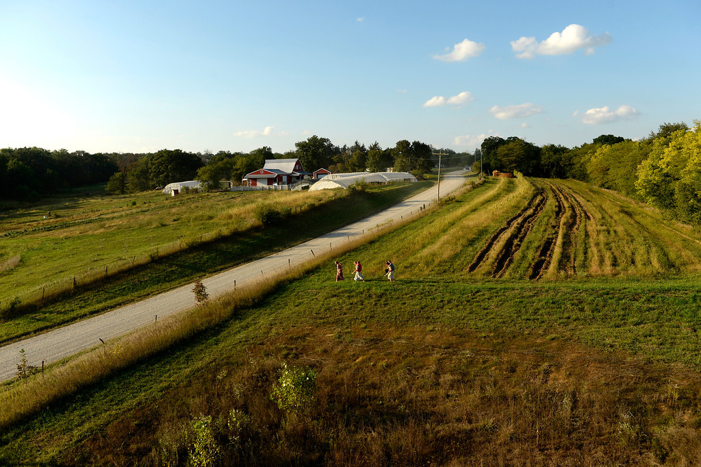 . After picking a few potatoes to be used at dinner the Newman girls head back home to their family farm in Trenton, Mo., Wednesday, September 25, 2013. A county road runs between the land the family farms. (Photo By RJ Sangosti/The Denver Post)