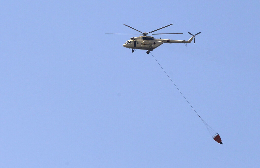 ". An Egyptian army helicopter transports water to hose down fires at a police officers\' club and the Egyptian Soccer Federation after Al Ahly fans, also known as ""Ultras\"" set fire to them following a court verdict, in Cairo March 9, 2013.  REUTERS/Amr Abdallah Dalsh"