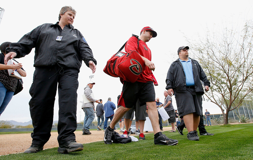 . Flanked by two security guards, Arizona Diamondbacks\' Paul Goldschmidt walks back to the team clubhouse after signing autographs for fans after an informal workout with teammates a day prior to MLB spring training baseball starting for pitchers and catchers at the Diamondbacks spring training facility, Thursday, Feb. 6, 2014, in Scottsdale, Ariz. (AP Photo/Ross D. Franklin)