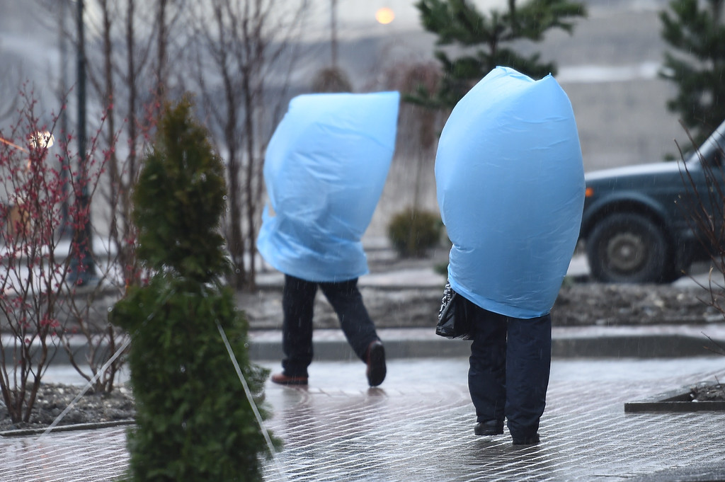 . Workers protect themselves from heavy rain as they walk to the media center during the Sochi Winter Olympics on February 18, 2014. LEON NEAL/AFP/Getty Images