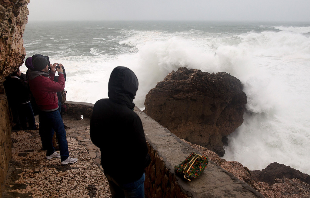 . People watch waves breaking against the rocks near North beach or Praia do Norte on January 6, 2014 in Nazare, Portugal. Strong winds and big waves are expected along the coastline of Portugal and Galicia in Spain for today. The waves at Praia do Norte are famed for being amongst the biggest in the World and it is a popular spot for daredevil big-wave surfers.  (Photo by Pablo Blazquez Dominguez/Getty Images)