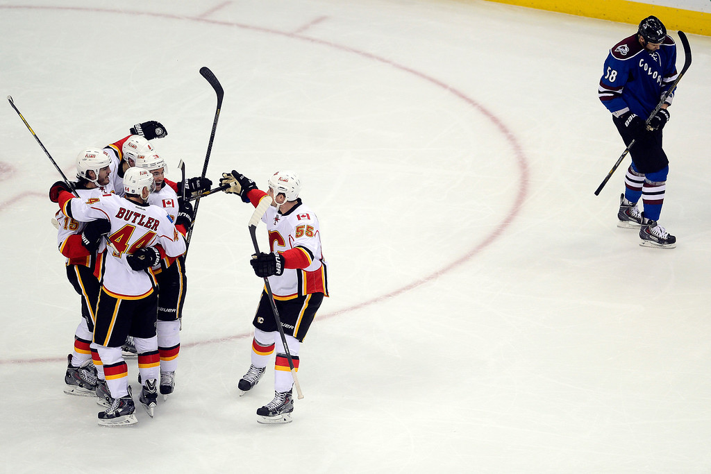 . The Calgary Flames celebrate a goal by Joe Colborne (8) as Patrick Bordeleau (58) of the Colorado Avalanche skates off the ice during the second period.  (Photo by AAron Ontiveroz/The Denver Post)