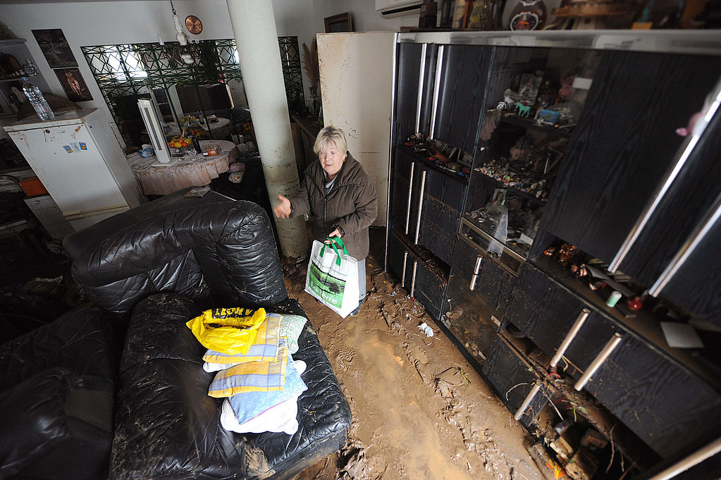 """. A woman cleans her house on Januray 20, 2014 in La Londe-les-Maures, southeastern France. River levels were receding early today in southeastern France after \""""historic\"""" floods left two people dead and more than 150 were airlifted to safety. A third man disappeared while out on his boat and 4,000 homes have been left without power after the deluge in the department of Var, they said. Local official Laurent Cayrel said one of the victims, a 73-year-old man, died in his basement, while the other was swept away in his car.  AFP PHOTO / BORIS HORVATBORIS HORVAT/AFP/Getty Images"""