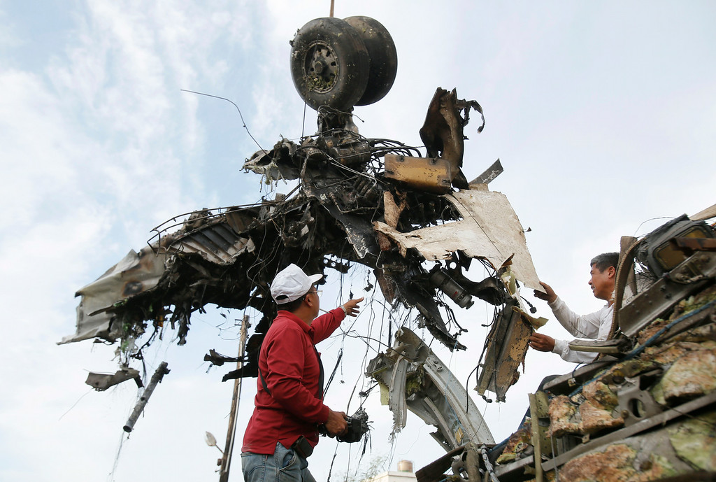 . Emergency workers remove the wreckage of crashed TransAsia Airways flight GE222 on the outlying island of Penghu, Taiwan, Thursday, July 24, 2014. Stormy weather on the trailing edge of Typhoon Matmo was the likely cause of the plane crash that killed more than 40 people, the airline said Thursday. (AP Photo/Wally Santana)