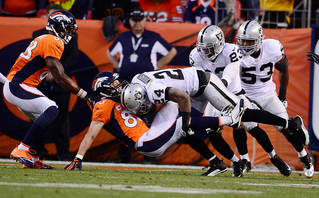 . Denver Broncos wide receiver Wes Welker (83) is tackled by Oakland Raiders free safety Charles Woodson (24) in the first quarter. The Denver Broncos took on the Oakland Raiders at Sports Authority Field at Mile High in Denver on September 23, 2013. (Photo by AAron Ontiveroz/The Denver Post)