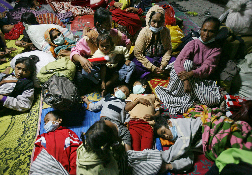 . Villagers who were evacuated from their homes following Mount Sinabung\'s eruption rest in a temporary shelter in Tiga Nderket, North Sumatra, Indonesia, Monday, Nov. 4, 2013. The 2,600-meter (8,530-foot) -high volcano has been erupting since Sunday, unleashing volcanic ash high into the sky and forcing the evacuation of villagers living around its slope. (AP Photo/Binsar Bakkara)