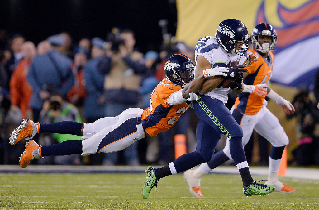 . Denver Broncos cornerback Champ Bailey (24) gets a hold of Seattle Seahawks wide receiver Doug Baldwin (89) during the fourth quarter in Super Bowl XLVIII at MetLife Stadium in East Rutherford, New Jersey Sunday, February 2, 2014. (Photo by Joe Amon/The Denver Post)