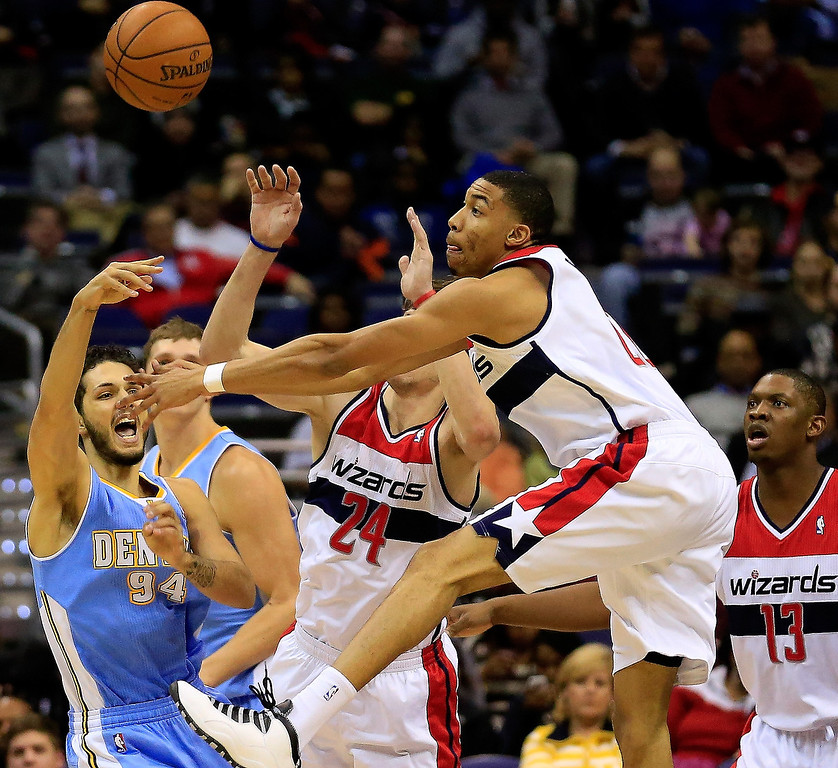 . Evan Fournier #94 of the Denver Nuggets passes the ball around Otto Porter Jr. #22 of the Washington Wizards during the first half at Verizon Center on December 9, 2013 in Washington, DC.    Photo by Rob Carr/Getty Images)