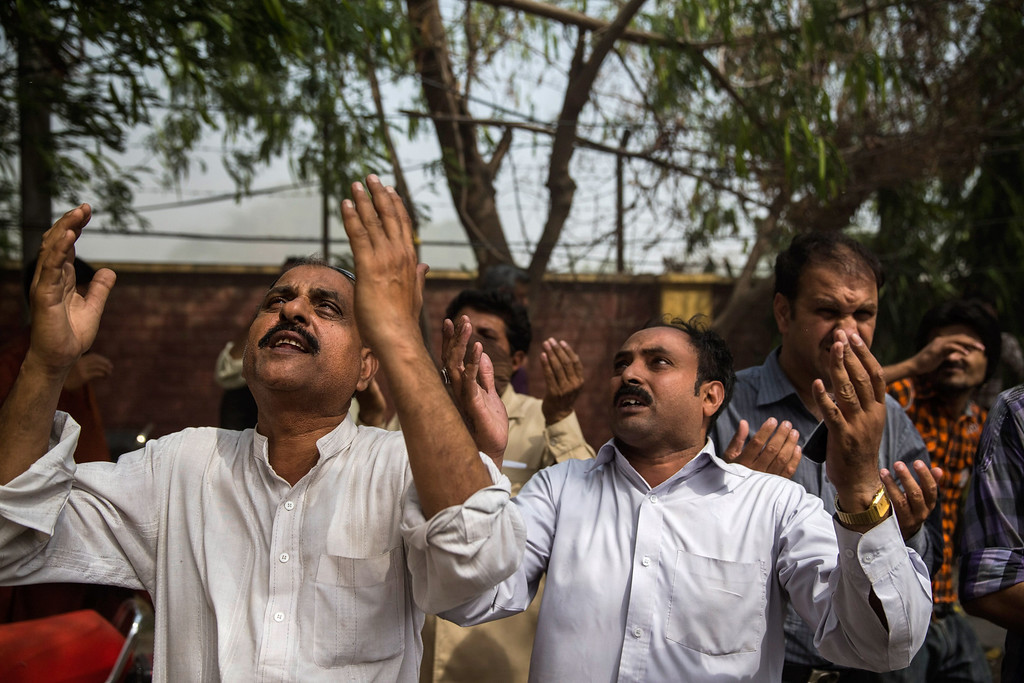 . People pray as they watch a man perched on a window ledge minutes before he was overcome by smoke and fell as a fire burns at the Lahore Development Authority (LDA) Plaza on May 09, 2013 in Lahore, Pakistan. (Photo by Daniel Berehulak/Getty Images)