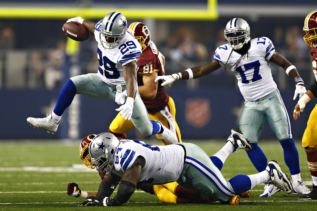 . ARLINGTON, TX - OCTOBER 13:  DeMarco Murray #29 of the Dallas Cowboys jumps over a tackle during the first half of a game against the Washington Redskins at  AT&T Stadium on October 13, 2013 in Arlington, Texas.  (Photo by Wesley Hitt/Getty Images)