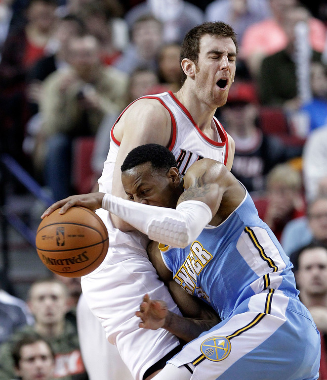 . Denver Nuggets guard Andre Iguodala, right, collides with Portland Trail Blazers forward Victor Claver, from Spain, during the second half of an NBA basketball game in Portland, Ore., Wednesday, Feb. 27, 2013.  Iguodala scored 29 points as Denver beat Portland 111-109. (AP Photo/Don Ryan)