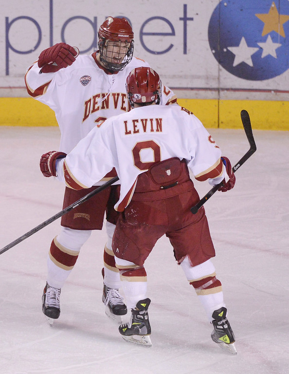 . DENVER, CO. - FEBRUARY 21, 2014: Denver wing Gabe Levin (9) congratulated center Quentin Shore (27) after he tied the game in the second period. The University of Denver hockey team hosted Colorado College at Magness Arena Friday night, February 21, 2014. Photo By Karl Gehring/The Denver Post