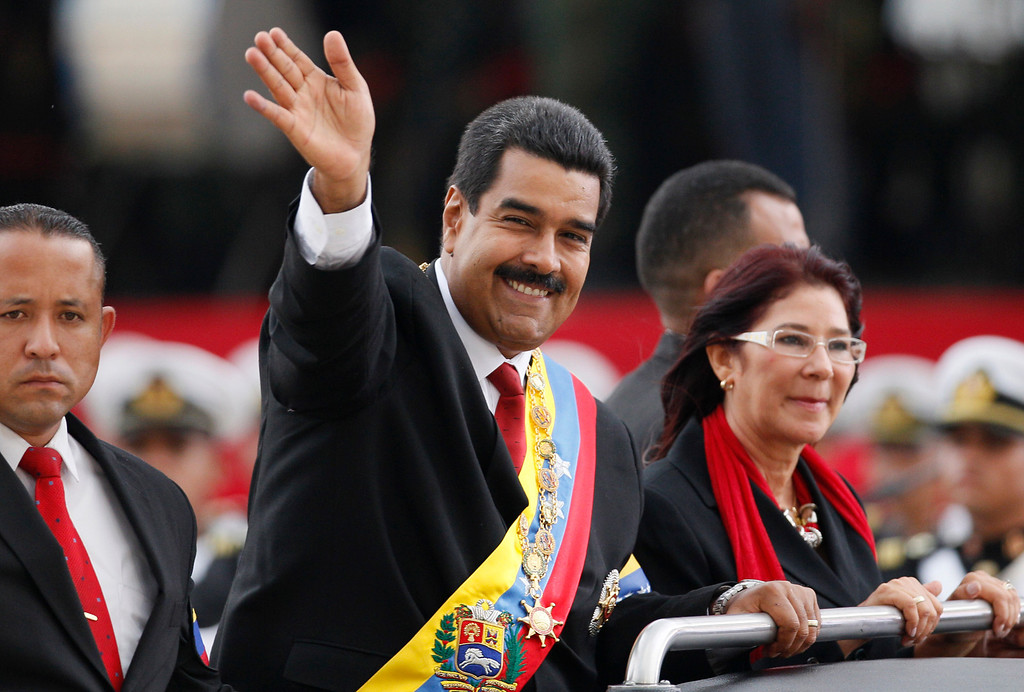 . Venezuela\'s President Nicolas Maduro waves from a vehicle, next to his companion Cilia Flores, during a military ceremony recognizing him as Commander-in-chief to the military at the Paseo Los  Proceres in Caracas, Venezuela, Friday, April, 19, 2013. Maduro, who has the support of the Chavista bases, needs all the momentum he can muster to consolidate control of a country struggling with shortages of food and medicines; chronic power outages; one of the world\'s highest homicide and kidnapping rates. (AP Photo/Ariana Cubillos)