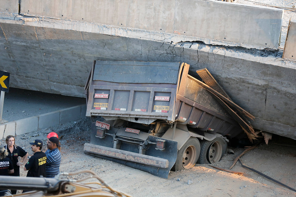 . A truck is trapped underneath a collapsed bridge in Belo Horizonte, Brazil, Thursday, July 3, 2014. The overpass under construction collapsed Thursday in the Brazilian World Cup host city. The collapse took place on a main avenue, the expansion of which was part of the World Cup infrastructure plan but, like most urban mobility projects related to the Cup, was not finished on time for the event. (AP Photo/Victor R. Caivano)
