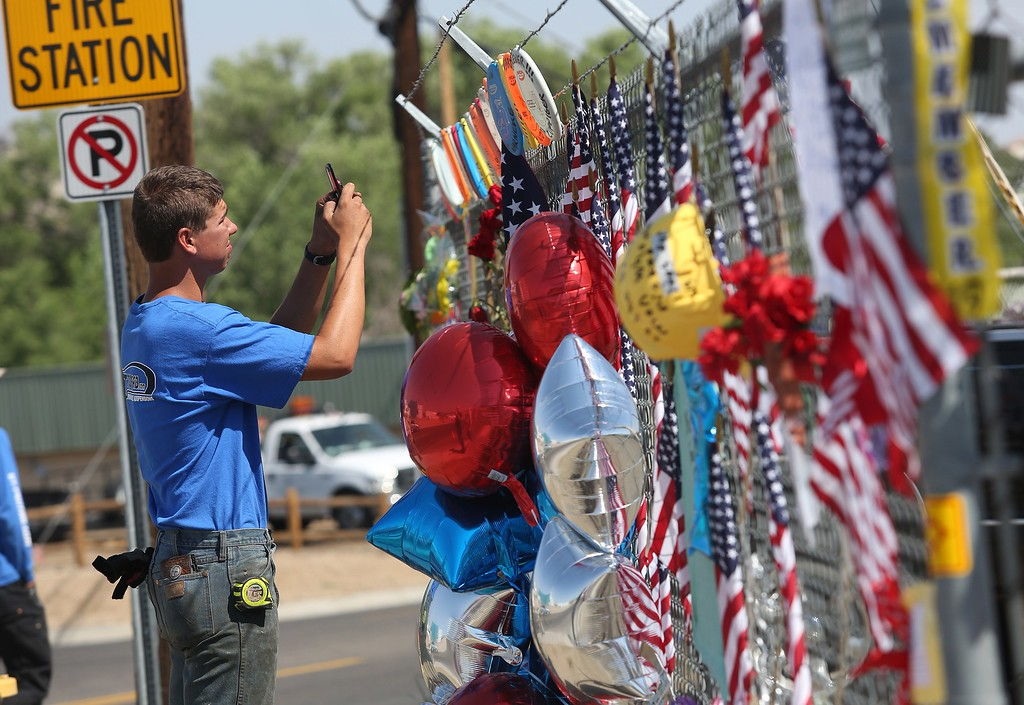. Local resident Garrett Rozendall takes pictures at the memorial for the 19 fallen Granite Mountain Hotshot firefighters outside of fire station 7 in Prescott, Arizona July 2, 2013. AFP PHOTO / KRISTA  Kennell/AFP/Getty Images