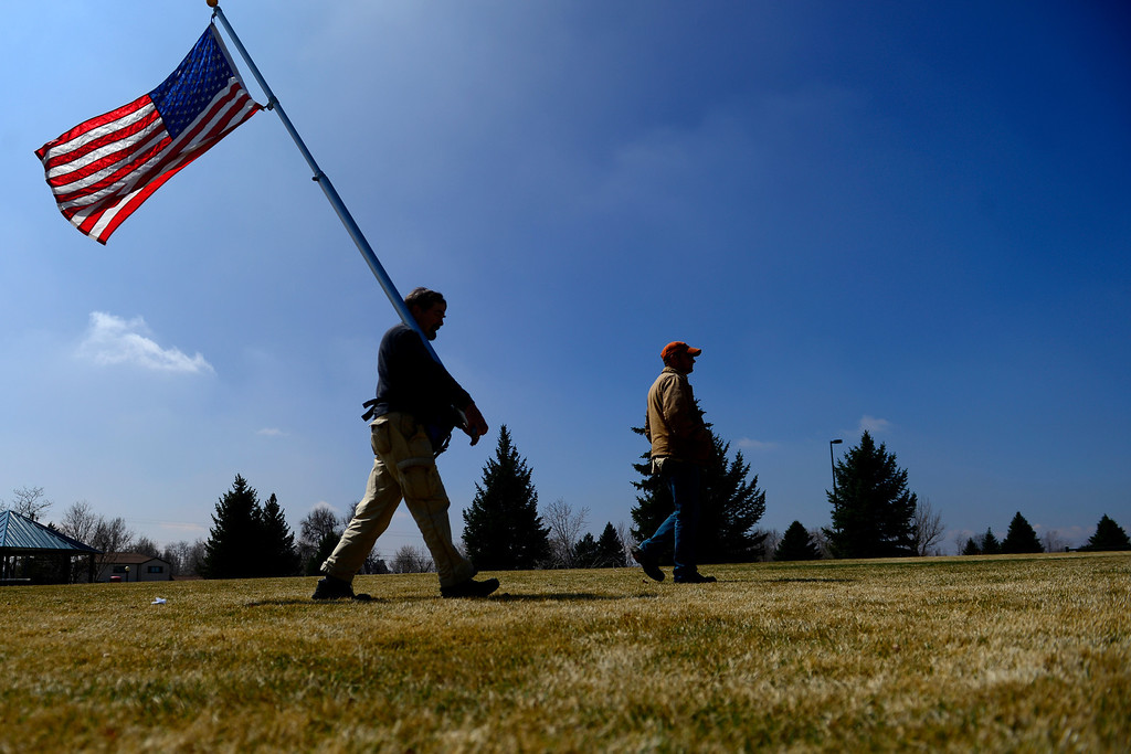 . DENVER, CO - APRIL 3: Jon Mackomber carries a flag as he and David Griffith walk towards a a gathering of Colorado sheriffs. Sheriffs from around the state gathered to speak out against gun control before President Barack Obama was set to give a speech at the Denver Police Academy about a mile away. (Photo by AAron Ontiveroz/The Denver Post)