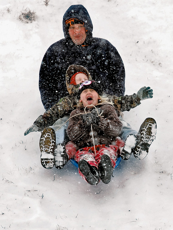 . Danielle, front, and Stephen Pilipovic scream along with father Roger as he family enjoys a sled ride down a hill, Tuesday, Jan. 28, 2014, as snow falls unexpectedly in the area causing school and government closings in Blount County, in Maryville, Tenn. (AP Photo/The Daily Times, Tom Sherlin)