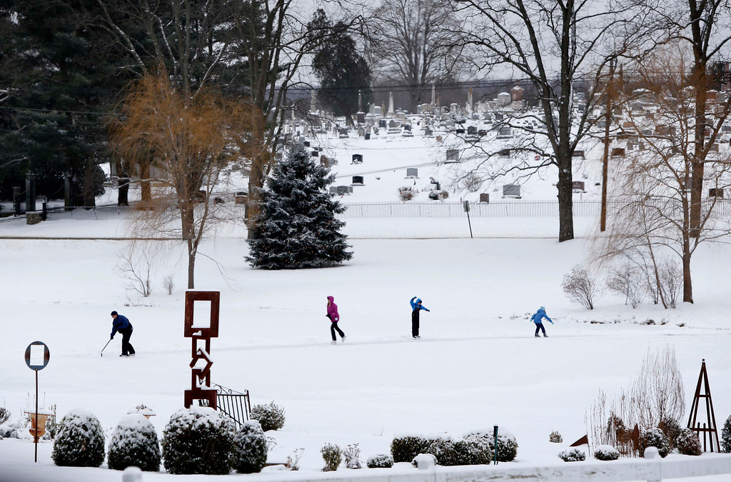 . A group of people skate on a frozen pond in Newtown, Conn., Saturday, Dec. 14, 2013.  (AP Photo/Robert F. Bukaty)
