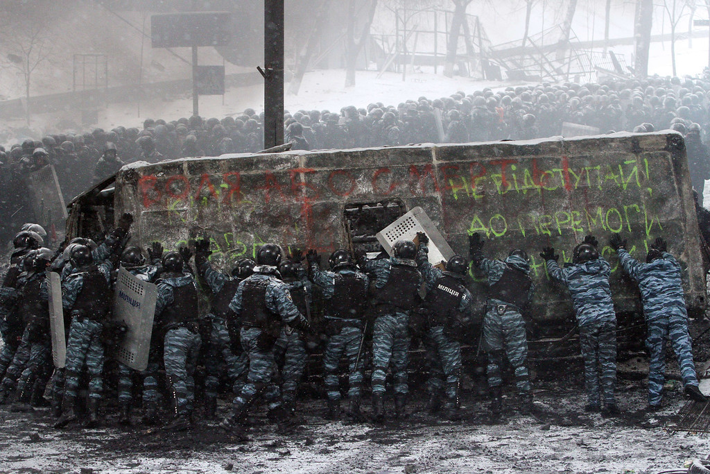 . Riot police officers push a police van destroyed by demonstrators during clashes in the center of Kiev on January 22, 2014. AFP PHOTO/ ANATOLII BOIKO/AFP/Getty Images