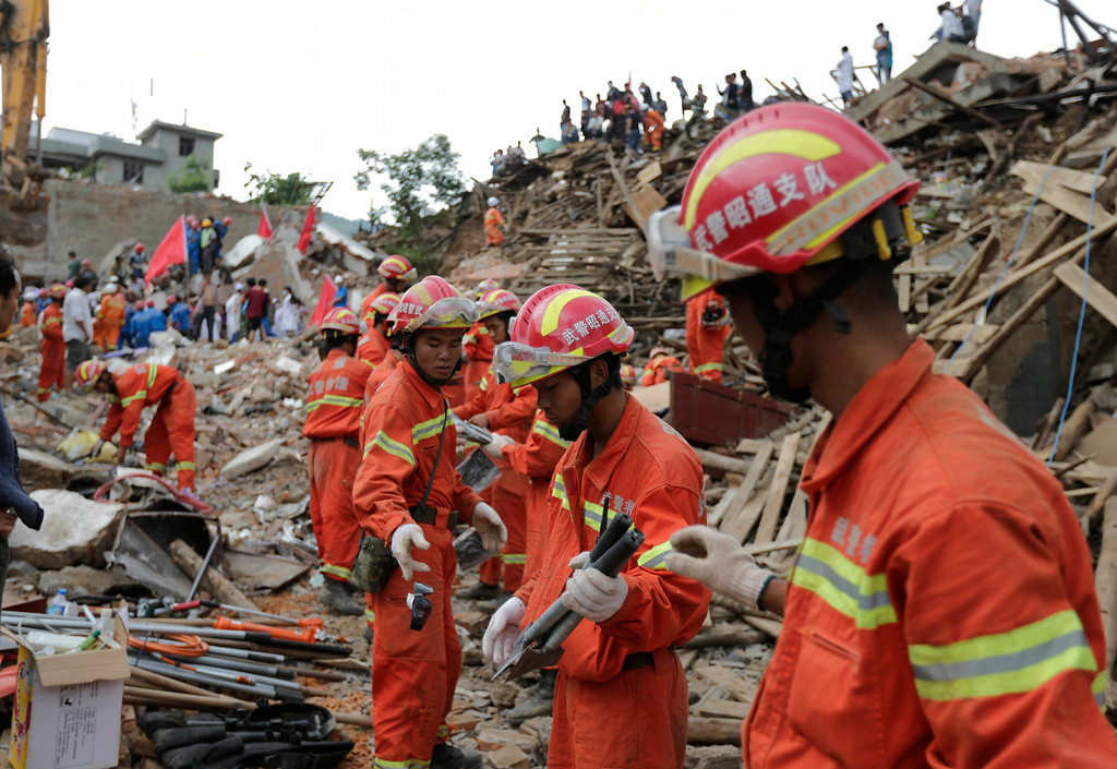 . Rescuers move away the tools from the rubbles as they search for survivors following a massive earthquake in the town of Longtoushan in Ludian County in southwest China\'s Yunnan Province Tuesday, Aug. 5, 2014.  (AP Photo/Andy Wong)