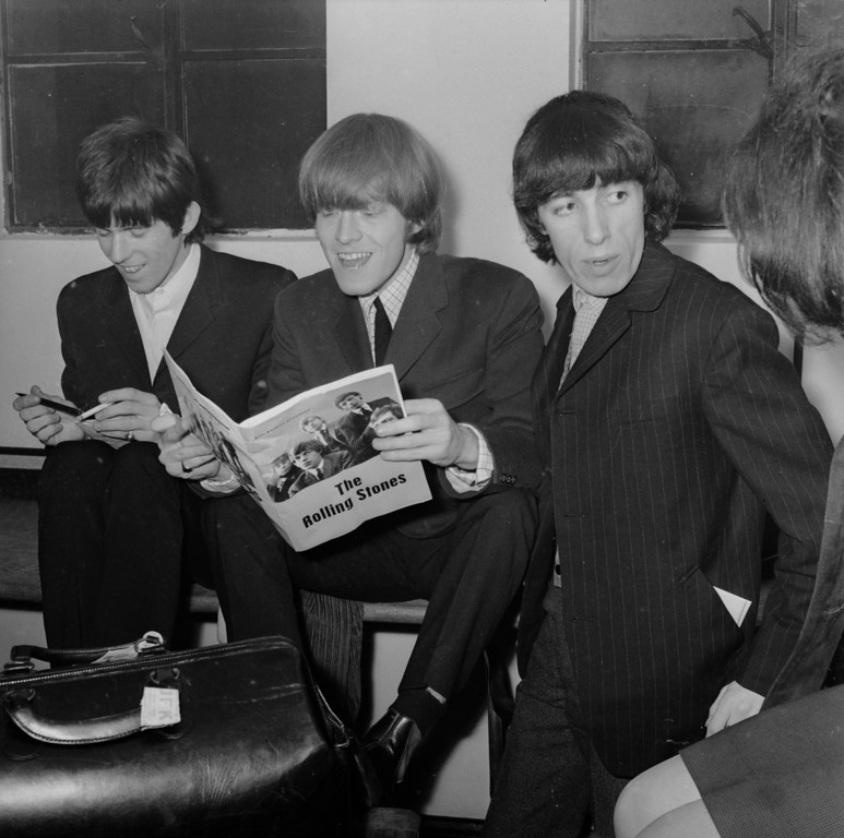 . Rolling Stones (left to right), Keith Richards, Brian Jones and Bill Wyman backstage before a concert. Jones is reading a fanzine dedicated to the group, January 1965.  (Photo by Keystone Features/Getty Images)