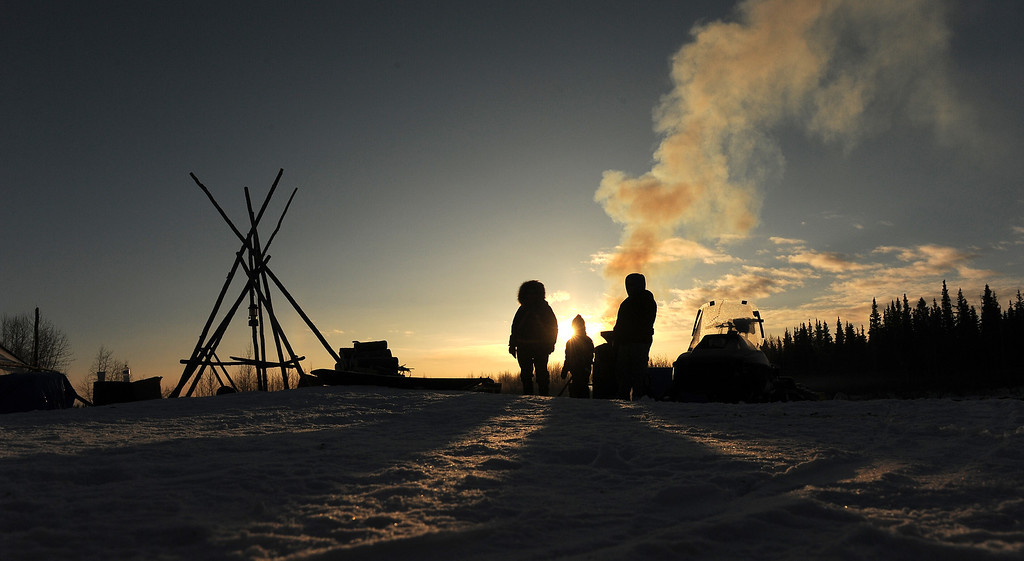 . Nikolai residents Oline Petruska, Tyler Alexia and Stephanie Petruska wait by the wood fired hot water for mushers to come in at the Nikolai checkpoint during the 2014 Iditarod Trail Sled Dog Race at sunrise on Wednesday, March 5, 2014. (AP Photo/The Anchorage Daily News, Bob Hallinen)
