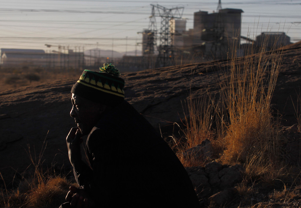 . An unidentified miner contemplates as he looks over the area where, a year ago, police opened fire on striking platinum miners killing 34 and injuring 78, before a memorial service to get under way, near the Marikana, South Africa, platinum mine, background, Friday Aug. 16, 2013.  The killings happened after days of clashes with mine security and police. The miners were demanding better salaries, working, housing and living conditions. (AP Photo/Denis Farrell)