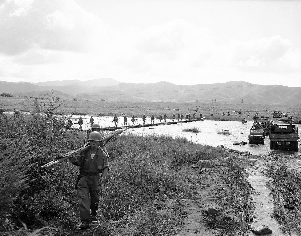 . Litter bearers move up as infantrymen of the U.S. 24th division cross foot-bridge over swollen stream on the east central front in Korea on Sept. 15, 1951. Jeeps and trucks are ferrying equipment and men across the stream. (AP Photo/George Sweers)