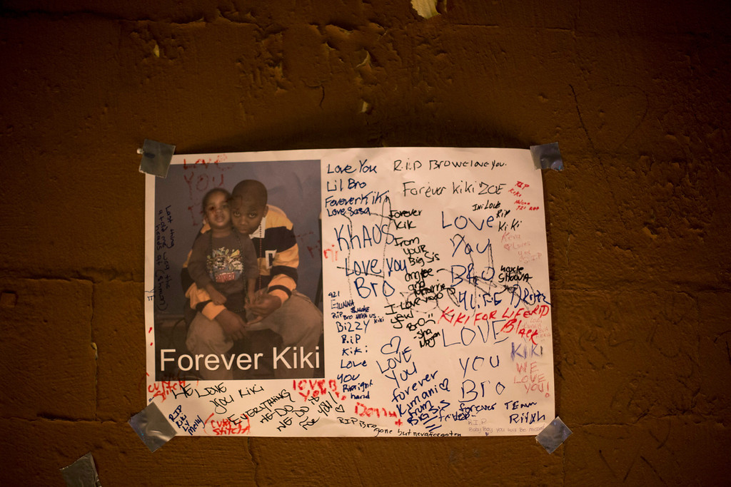 """. A sign with mourners\' notes hangs on a wall above a memorial for 16-year-old Kimani \""""Kiki\"""" Gray after he was killed in a New York Police Department shooting in the Brooklyn borough of New York, March 11, 2013. Picture taken March 11, 2013.  REUTERS/Lucas Jackson"""