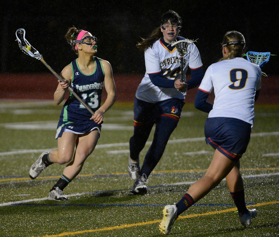 . LITTLETON, CO - MAY 8: Haley Kroll, left, ThunderRidge High School, looks for an opening against the defense of Kate Bitzko, center, and Jacqueline, Heritage/Littleton,during the second half of play at Littleton Public Schools Stadium for the first round of the 2013 Colorado Girls State Lacrosse Championships May 8, 2013. ThunderRidge won 8-5. (Photo By Andy Cross/The Denver Post)