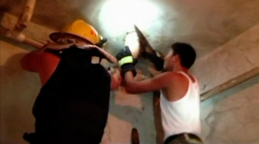. Firefighters saw a sewage pipe as they attempt to rescue an abandoned newborn baby boy, in this still image taken from video, in Jinhua city, Zhejiang province May 25, 2013. Firefighters in eastern China have rescued an abandoned newborn baby boy lodged in a sewage pipe directly beneath a toilet commode, state television reported, in a case which has sparked anger on social media sites. REUTERS/Local Firefighter Handout via CCTV/Reuters TV
