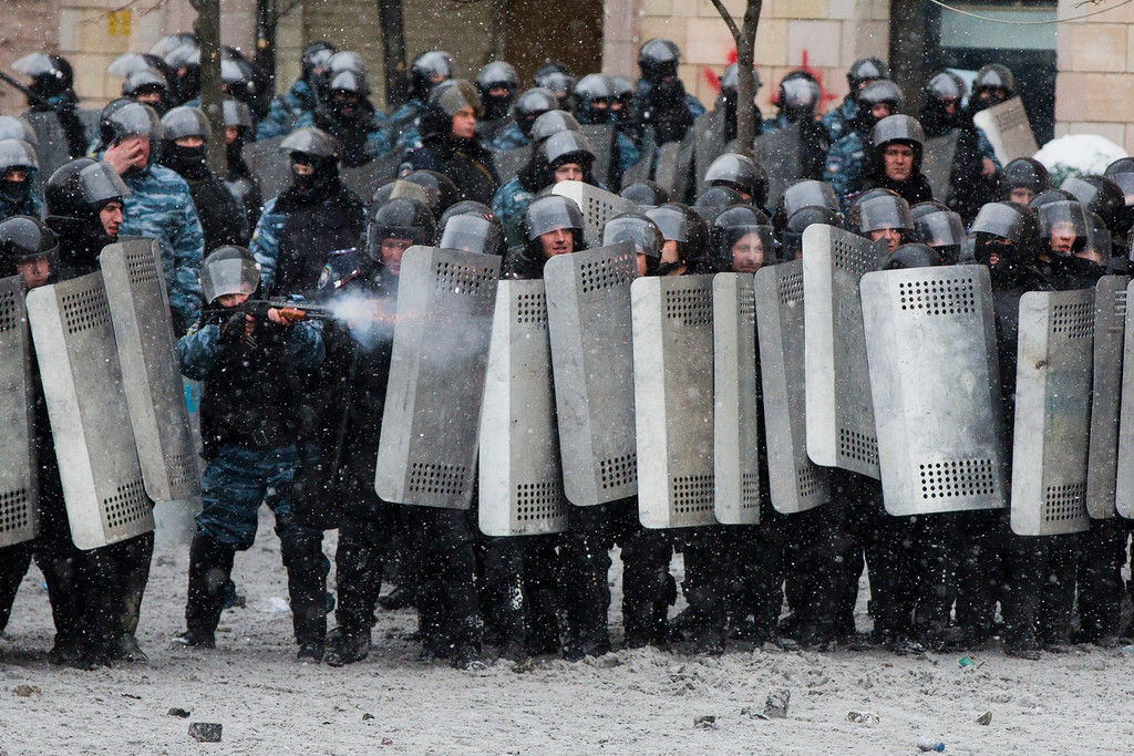 . A police officer uses a shotgun during clashes with protesters in central Kiev, Ukraine, Wednesday, Jan. 22, 2014. (AP Photo/Evgeny Feldman)