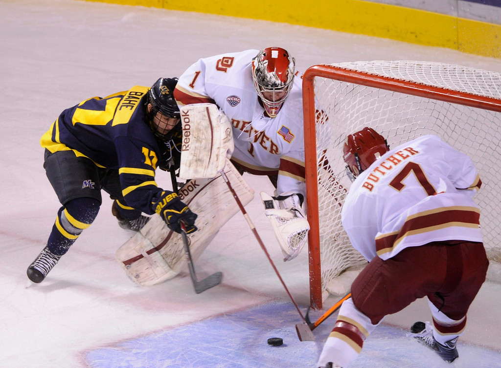 . DENVER, CO. - OCTOBER 12: Defenseman Will Butcher (7) came back to help goaltender Sam Brittain (1) after he got caught behind the net with Merrimack wing Ben Bahe (17) just outside the crease in the first period. The University of Denver hockey team hosted Merrimack at Magness Arena, Saturday night, October 12, 2013. Photo By Karl Gehring/The Denver Post