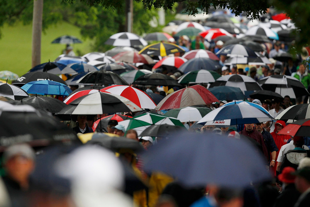 . Spectators leave the course under umbrellas after play was suspended for a second time for weather during the first round of the 2013 U.S. Open golf championship at the Merion Golf Club in Ardmore, Pennsylvania, June 13, 2013.  REUTERS/Matt Sullivan